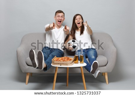 Excited cheerful couple woman man football fans cheer up support favorite team with soccer ball, pointing fingers on camera isolated on grey background. People emotions, sport family leisure concept #1325731037