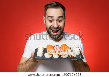 Excited cheerful young bearded man 20s wearing casual white t-shirt looking on makizushi sushi roll served on black plate traditional japanese food isolated on red color background studio portrait Stok fotoğraf ©