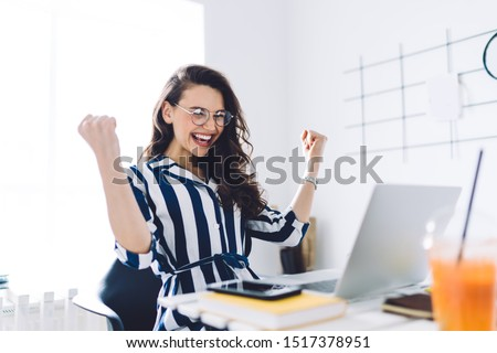 Excited cheerful young female in glasses and casual dress sitting at table with laptop and raising hands up and celebrating success