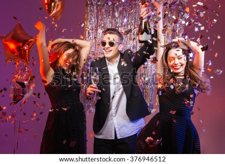 Excited cheerful young friends dancing and having party over purple background #376946512