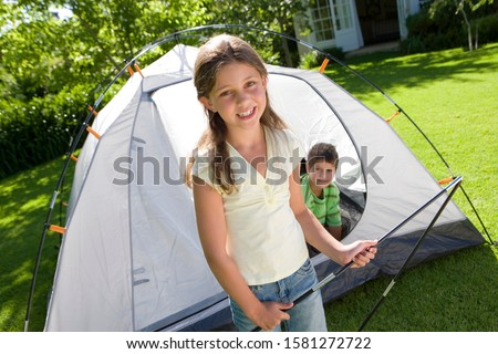 Excited children camping in garden putting up tent at camera