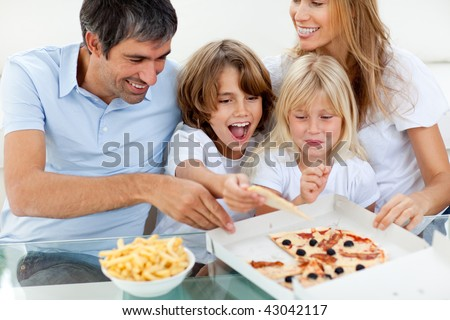 Excited children eating a pizza with their parents in the living-room