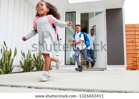 Excited Children Running Out Of Front Door On Way To School Watched By Father