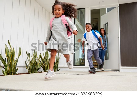 Excited Children Running Out Of Front Door On Way To School Watched By Mother