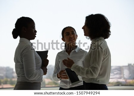 Excited colleagues discussing project near office window. Three businesswomen standing together and talking. Team discussion concept