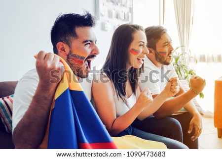 Excited colombian soccer fans looking a match at home - Shutterstock ID 1090473683