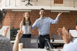 Excited company boss or team leader introducing new employee to colleagues in office welcoming hired newcomer member congratulating with promotion applauding celebrating reward, supporting coworker