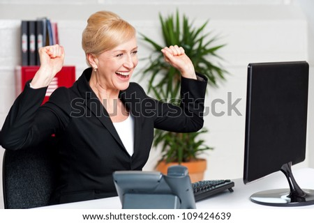 Excited corporate lady with raised arms looking at computer screen