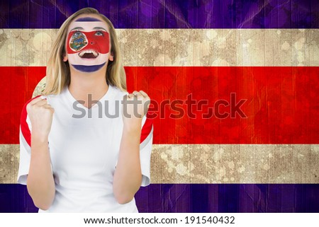 Excited costa rica fan in face paint cheering against costa rica flag in grunge effect