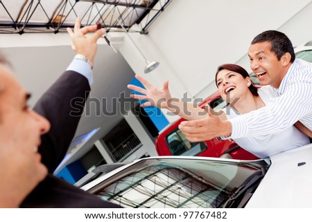 Excited couple buying a car and reaching for the keys