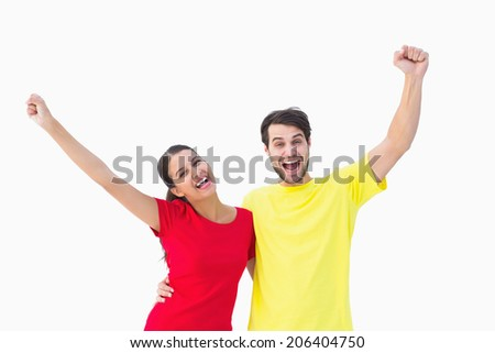 Excited couple cheering in red and yellow tshirts on white background