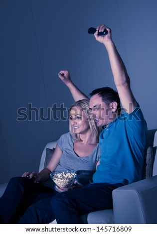 Excited Couple Watching Television And Eating Popcorn