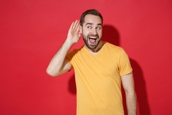 Excited curious young bearded man guy in casual yellow t-shirt posing isolated on red wall background studio portrait. People lifestyle concept. Mock up copy space. Try to hear you listening intently