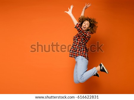 excited curly woman in a checkered shirt and jeans standing over an orange background with empty space for text next to her jumping of happiness #616622831