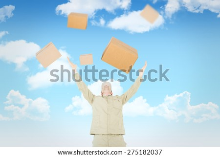 Excited delivery man with arms raised looking up against blue sky