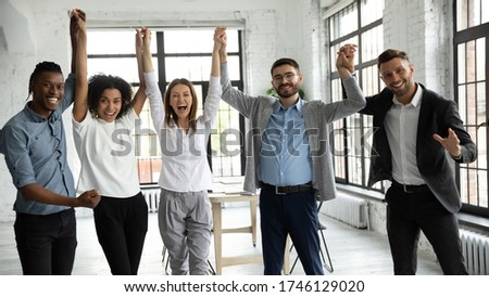 Excited diverse business people celebrating success, holding raised hands, looking at camera, smiling overjoyed employees team rejoicing achievement, laughing and screaming with joy in office room