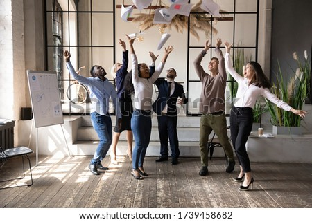 Excited diverse business people throwing papers, celebrating sharing teamwork success, laughing and screaming with joy, employees colleagues rejoicing business achievement in modern office room