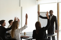 Excited diverse company employees raise hands answer question interact with positive confident african American coach, businesspeople colleagues volunteer involved in teambuilding activity at training