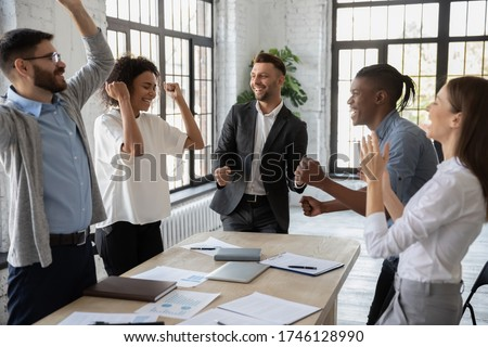 Excited diverse employees celebrating great teamwork result at meeting, sharing success, business achievement, happy colleagues laughing, rejoicing victory, standing in modern office together