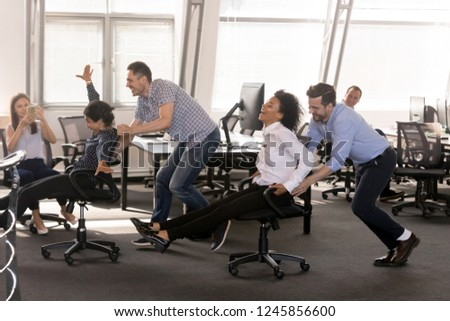 Excited diverse employees having fun together in office, riding on chairs at work, enjoying break, laughing, colleagues shoot video on phone, engaged funny activity, celebrating corporate success #1245856600