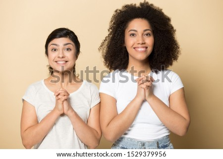 Excited diverse millennial girlfriends isolated on orange brown studio background keep hands in prayer hope for best luck, superstitious smiling multiethnic female friends feel hopeful look at camera #1529379956