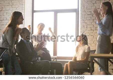 Excited diverse team people applauding celebrating success supporting leader telling great news, happy multi-ethnic employees sales group congratulating colleague with business achievement or reward