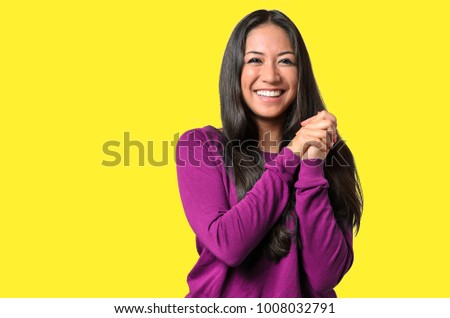 Excited elated young woman clasping her hands with a beaming smile of delight, Before Candy Background