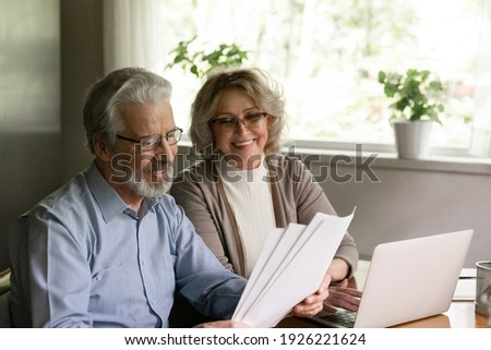 Excited elder family pensioner couple read and check financial document, calculate profit, saving income from investment. OAP Senior man and 50s woman do monthly paperwork, make utility payment online