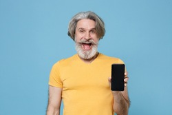 Excited elderly gray-haired mustache bearded man in casual yellow t-shirt posing isolated on blue background. People lifestyle concept. Mock up copy space. Hold mobile phone with blank empty screen