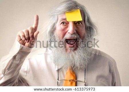 Excited elderly man with a sticky note on his forehead #613375973