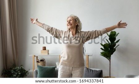 Excited elderly mature retired woman dancing in living room with widely opened outstretched arms, enjoying freedom. Overjoyed happy older female pensioner satisfied with leisure weekend time at home.