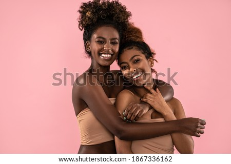 Excited emotional young women posing together , smiling and looking at camera. Pink pastel studio background. Beauty portrait of two afro female models. Perfect toothy smiles.