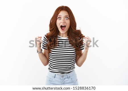 Excited emotive and thrilled gorgeous redhead girl in striped t-shirt, stare camera surprised and amazed, gasping drop jaw fantastic news, fist pump, triumphing, achieve success, win prize