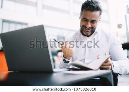Excited entrepreneur 40s dressed in white shirt satisfied with business results, happy Caucasian male proud CEO with personal planner celebrating projecting goal sitting at sidewalk table with netbook
