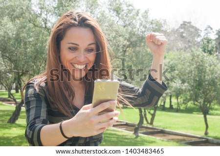 Excited euphoric lady with smartphone celebrating great news Happy woman staring at phone screen in surprise, smiling and raising fist in win gesture. Surprising good news or concept #1403483465