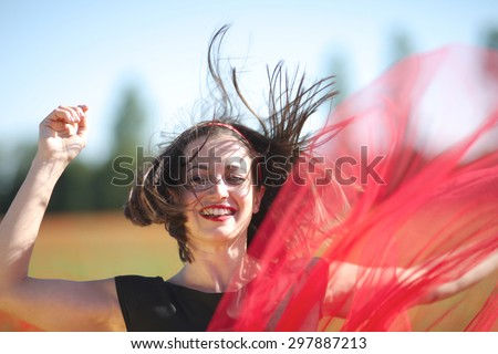 Excited face of a jumping woman with flying hair and skirt