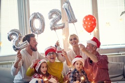 Excited family at New Year eve home party together in festive atmosphere. New Year, holiday, family time together
