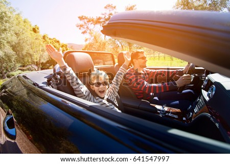 excited family of two, young father and his smiling son with hands high up in the air, enjoying road trip in convertible car, journey and vacation concept, sun flare #641547997