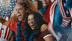 Excited fans with US flag in sports crowd celebrating on team success. Group of American soccer fans cheering in stands.