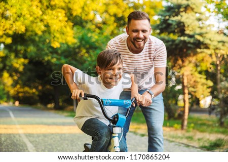 Excited father and his son having fun together at the green park, teaching son how to ride a bicycle