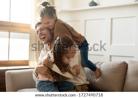 Excited father having fun with two little daughters, spending weekend at home, sitting on comfortable couch, laughing cute preschool girls and dad hugging, cuddling, enjoying free time together