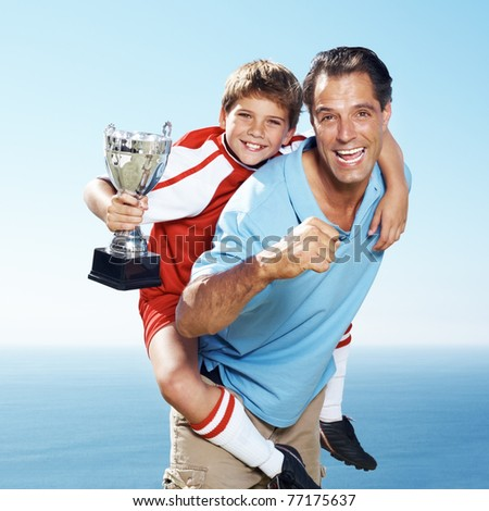 Excited father piggybacking his champion footballer son with a first prize tropy