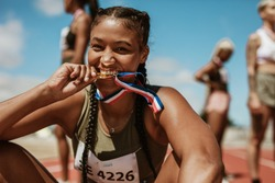Excited female athlete biting her medal while sitting on race track with other athletes in background. Sports woman enjoying winning a medal in sprinting event at stadium.