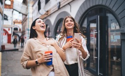 Excited female friends smiling broadly especially in unrestrained manner during cellphone networking, grinning hipster girls with smartphone and coffee to go satisfied with meeting for mobility