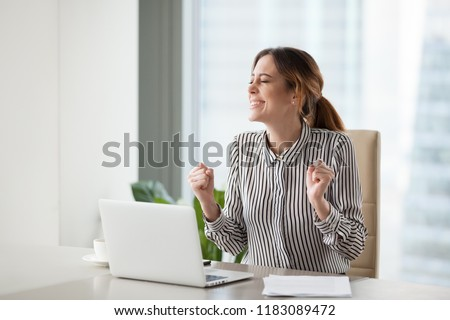Excited female office worker happy winning online lottery or getting promotion, smiling businesswoman making yes gesture celebrating company online success or rising sales. Concept of reward