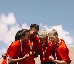 Excited female soccer players shouting in joy after winning the championship. Woman football team with medals celebrating victory.
