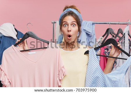 Excited female wearing scarf on head, looking with bugged eyes and jaw dropped out while holding two hangers with dresses in both hands being astonished by low prices and high quality of clothes