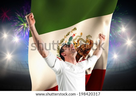 Excited football fan cheering against fireworks exploding over football stadium and mexico flag