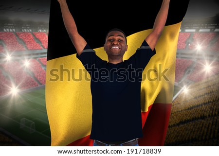 Excited football fan in black cheering holding belgium flag against vast football stadium with fans in yellow and red