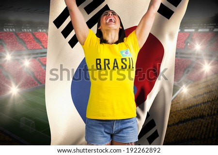 Excited football fan in brasil tshirt against holding south korea flag vast football stadium with fans in yellow and red